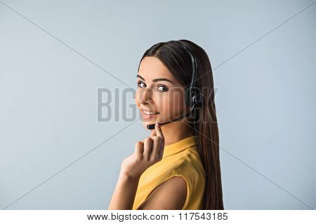 Photo of beautiful young call center operator standing near gray background. Woman with headphones looking at camera and smiling