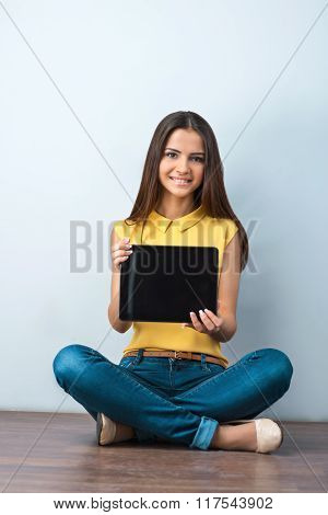 Photo of beautiful young business woman sitting on wooden floor. Smiling woman with yellow shirt showing tablet computer and looking at camera