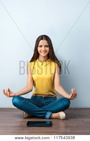Photo of beautiful young business woman sitting on wooden floor. Smiling woman making lotus position near tablet computer