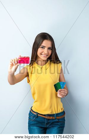 Photo of beautiful young business woman standing near gray background. Woman with yellow shirt looking at camera, smiling and showing credit cards