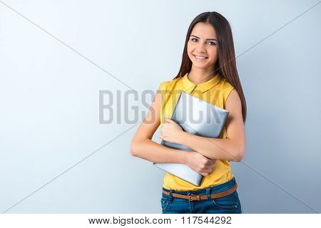 Photo of beautiful young business woman standing near gray background. Smiling woman with yellow shirt holding laptop and looking at camera