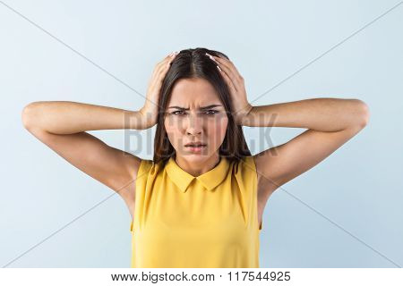 Photo of beautiful young business woman standing near gray background. Stressed woman with yellow shirt having headache