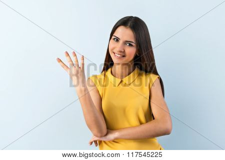 Photo of beautiful young business woman standing near gray background. Smiling woman with yellow shirt looking at camera and showing four fingers