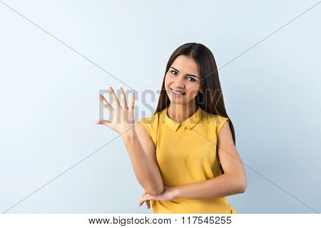 Photo of beautiful young business woman standing near gray background. Smiling woman with yellow shirt looking at camera and showing five fingers