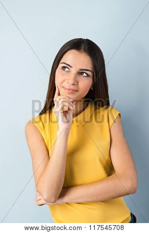 Photo of beautiful young business woman standing near gray background. Woman with yellow shirt looking aside