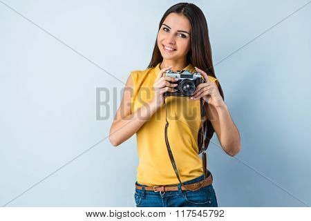 Photo of beautiful young business woman standing near gray background. Woman with vintage camera looking at camera and smiling