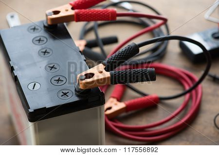 A Car battery with red and black battery Jumper Cables with copper clamps attached to the terminals. Automotive battery on a work desk with tools in background. poster