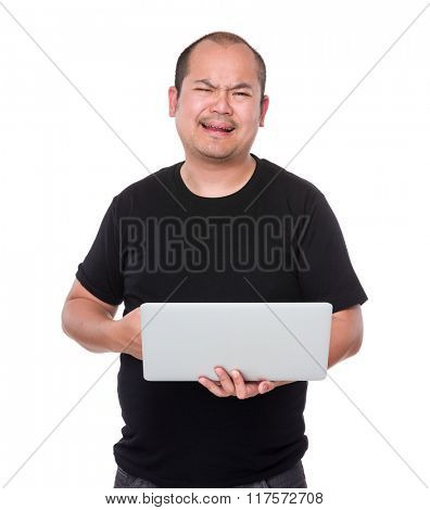 Unhappy man holding laptop computer