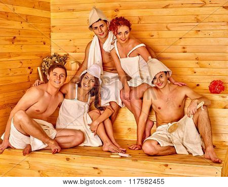 Group people in hat relaxing at sauna. Men and women posing at camera.