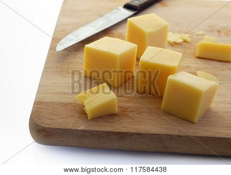 yellow cheese on cutting board with knife