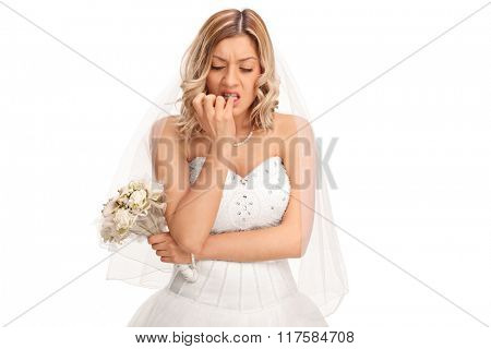 Young nervous bride in a white wedding dress biting her fingernails isolated on white background