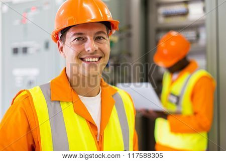 close up portrait of industrial technician in front of co-worker