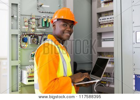 modern african electrical worker using laptop computer in control room