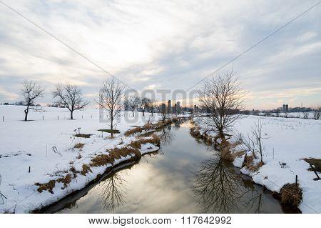 Creek Flowing Through Snowy Field