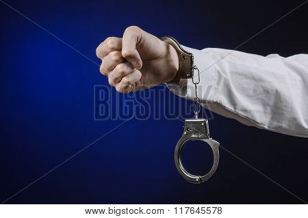 Dishonest And A Prison Doctor Topic: The Hand Of Man In A White Shirt With Handcuffs On A Dark Blue
