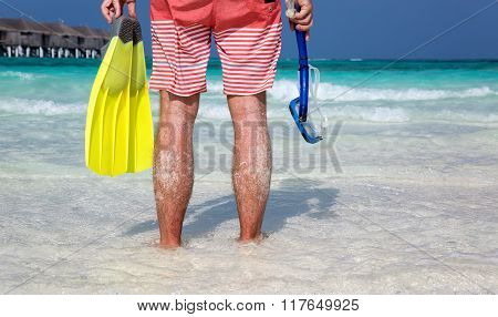Man with snorkeling gear in his hands standing on a Maldivian beach