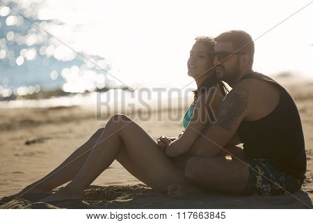 Romantic couple in hug watching sunrise/ sunset together.Young man and woman in love hugging