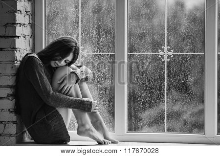 Beautiful young woman sitting alone close to window with rain drops. Sexy and sad girl. Concept of l