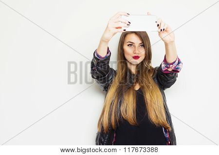 Teenage girl in black taking a selfie on cellphone