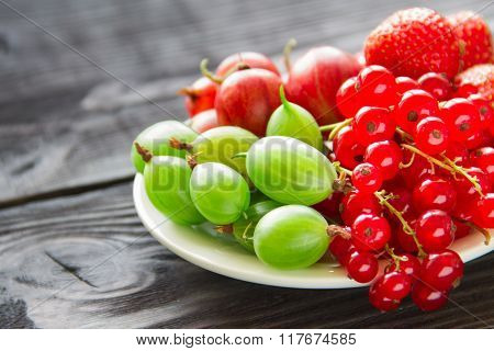 Berries In Plates, On A Wooden Table