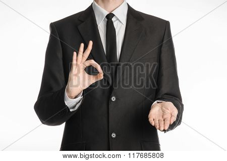 Businessman And Gesture Topic: A Man In A Black Suit With A Tie Showing Okay Sign With His Left Hand