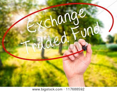 Man Hand Writing Exchange Traded Fund With Black Marker On Visual Screen.
