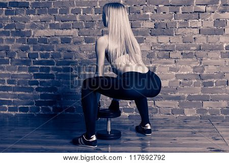 Attractive athletic woman in black leggins performing deadlift with dumbbell at the gym view from the back
