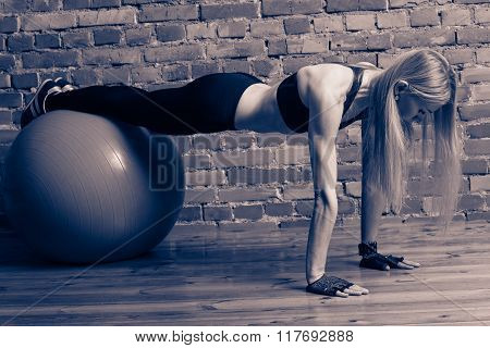 Attractive blond fitness model performing push ups with a fitball at the gym