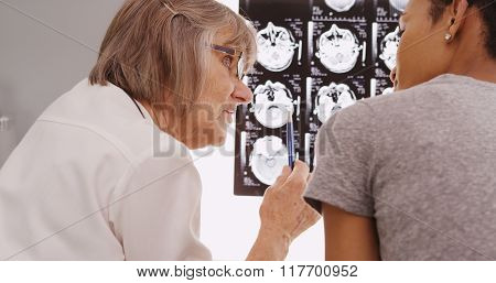 Mature Radiologist Reviewing X-ray Results With Patient