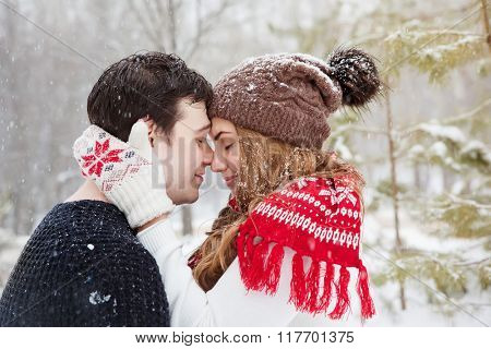 young couple in love enjoying a walk in winter park