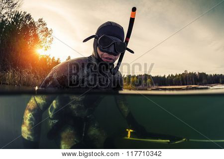 Underwater split shot of the fisherman in wet suit and with a speargun