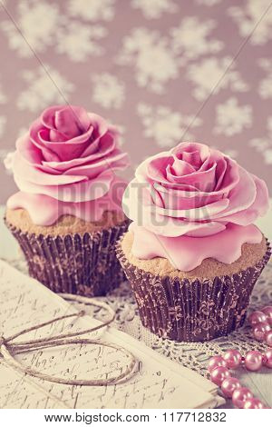 Two cupcakes with rose flowers and a letter
