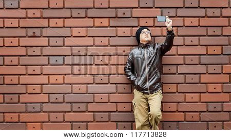 An Asian Man in a Brown Jacket with His Smartphone