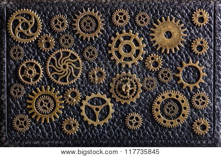 steampunk mechanical cogs gears wheels on leathern background