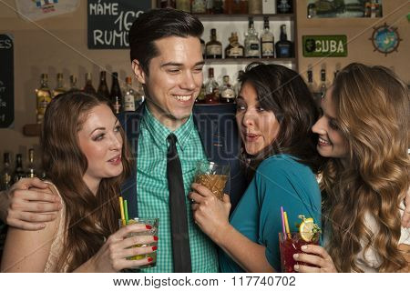 Irresistibly attractive man flirting simultaneously with three women.