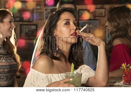 Woman looks at you while taking a pull on her cigarette and holding a glass with mojito in her hand. her friends are dancing and chatting in the background