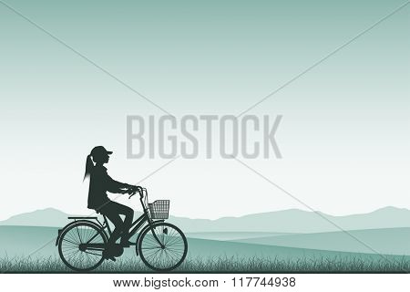 A Girl on a Bicycle in Silhouette with Meadow Landscape