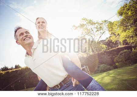 Husband giving piggy back to wife in the garden