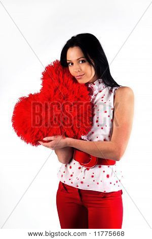 Young Beautiful Brunette Hugs A Big Soft Heart. Feast Of St. Valentine's Day.