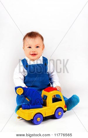 Happy Little Boy Playing With Cars And Toys.