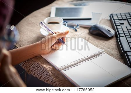 People Taking Mobile Phone And  Top Table Working By Writing On White Empty Paper Page With Left Han