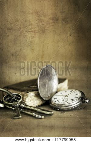 Vintage grunge still life with pocket watch, old book and brass keys.