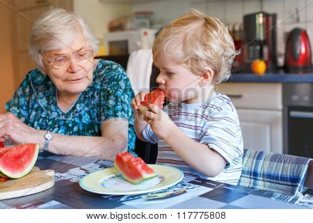 Little toddler boy and great grandmother eating watermelon