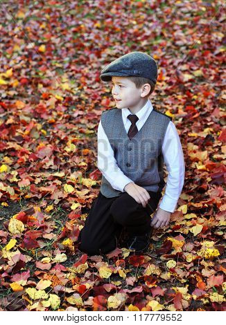 Little boy kneels amid a carpet of red and yellow leaves in Southern Arkansas. He is wearing a tam vest tie and white shirt.