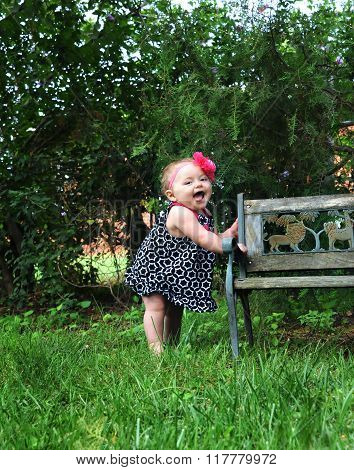Baby girl holds onto a wooden bench and expresses her joy by gurgling and cooing. She is barefoot and wearing a sundress. Pink flower band encircles her head.