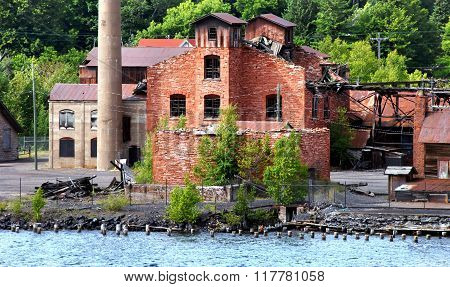 Historic Quincy Copper Smelter lays abandoned and empty. Buildings have fallen into ruin with rusting metal and broken windows. Smelter sits on the shore of the Portage Lake near Hancock Michigan.