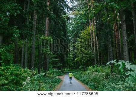Man running on path in old green forest.