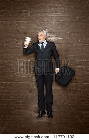 Top view creative photo of senior businessman on vintage brown wooden floor. Businessman holding case with documents and cup of coffee