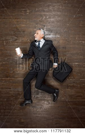 Top view creative photo of senior businessman on vintage brown wooden floor. Businessman holding case with documents and cup of coffee. Businessman is in a hurry