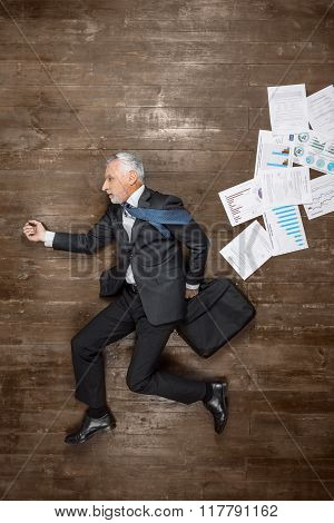 Top view creative photo of senior businessman on vintage brown wooden floor. Businessman holding case with documents. Businessman is in a hurry